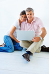 Smiling mature couple sitting at home and working on a laptop