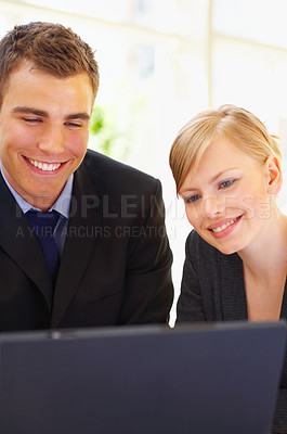 Buy stock photo Shot of two businesspeople working together on a laptop