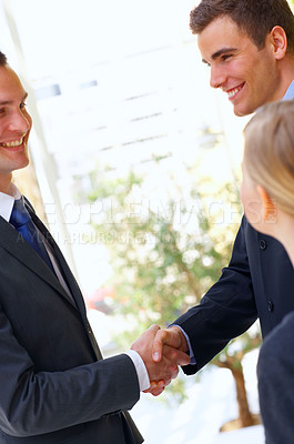 Buy stock photo Shot of two businessman shaking hands while a colleague looks on