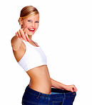 Happy young female in old jeans pant after losing weight and pointing towards the camera