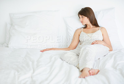 Buy stock photo Sad young woman missing somebody on bed