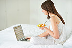 Young female using laptop and eating fruit salad