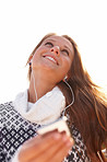 Happy young woman listening to music and looking up