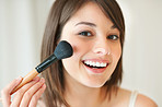 Lovely young woman applying make up on her face