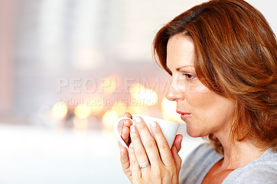 Buy stock photo Young woman sipping coffee by the fireplace