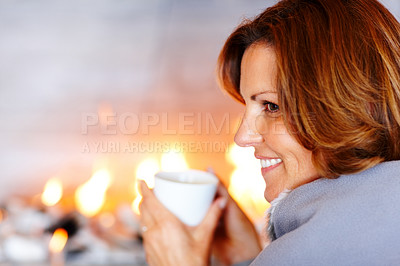 Buy stock photo A pretty young woman enjoying a cup of coffee at home by the fireplace
