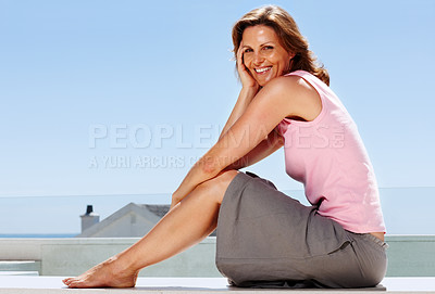 Buy stock photo Happy young woman posing while sitting on the terr