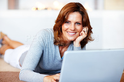 Buy stock photo Beautiful young woman using laptop while lying on