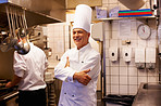 Confident male cook with trainee in kitchen