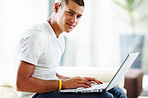 Happy young man sitting and working on laptop