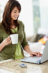 Cute brunette working on a laptop , having coffee at home