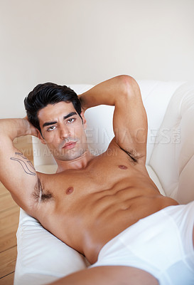 Buy stock photo Portrait of a handsome young male underwear model posing on sofa
