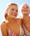 Closeup of two happy pretty women smiling against sky on a sunny day