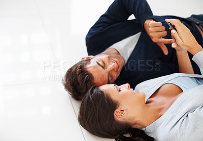 Buy stock photo Attractive couple on the floor holding a cell phone