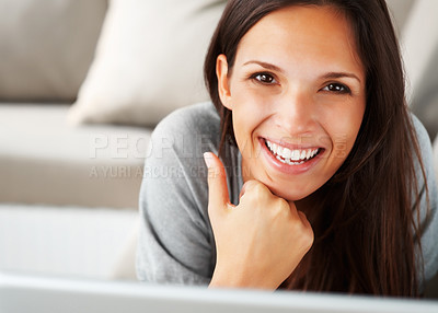 Buy stock photo Pretty woman lying on sofa with chin on fist