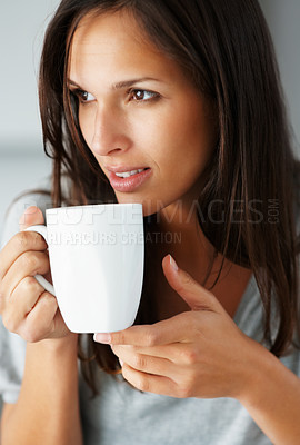 Buy stock photo A pretty woman daydreaming while holding a cup of coffee