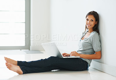 Buy stock photo Pretty woman sitting against wall with laptop