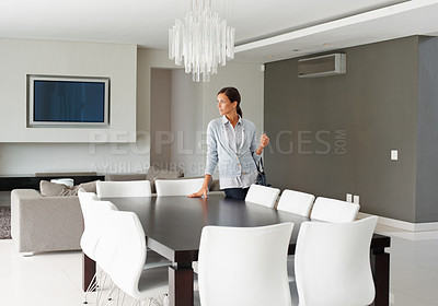 Buy stock photo Pretty woman standing in modern dining room looking outward