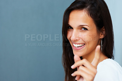 Buy stock photo Pretty woman smiling and pointing against blue background