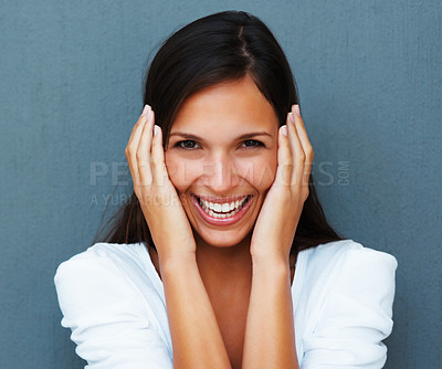 Buy stock photo Woman with hands against cheeks against blue background