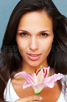 Buy stock photo Head shot of pretty woman holding a flower looking directly in camera