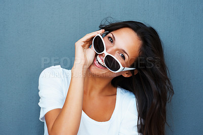 Buy stock photo Pretty woman wearing sunglasses while tilting head to the side