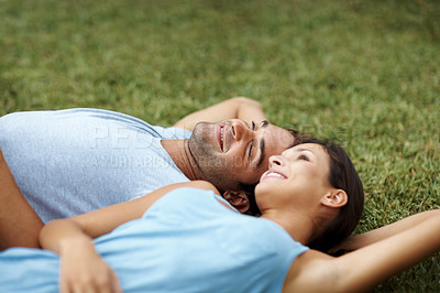 Buy stock photo Portrait of a happy young couple lying on grass in a park - Outdoor