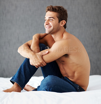 Buy stock photo Shot of a shirtless young man sitting on a bed at home