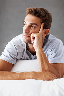 Buy stock photo Shot of a thoughtful young man relaxing on a bed at home