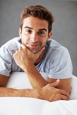 Buy stock photo Portrait of a handsome young man lying on a bed at home