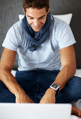 Buy stock photo Shot of a happy young guy working on a laptop at home