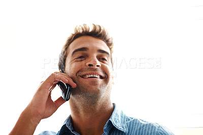 Buy stock photo Shot of a happy young man speaking on cellphone against bright background