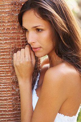 Buy stock photo Pretty young woman leaning against a palm tree trunk and looking away