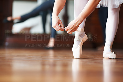 Buy stock photo Closeup portrait of a ballerina putting on pointes with a blurred man practicing in background