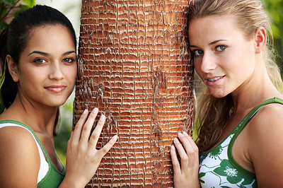 Buy stock photo Two attractive young women leaning against a tree trunk - Outdoor portrait