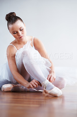 Buy stock photo Portrait of a ballerina dancer putting on her shoe - copyspace
