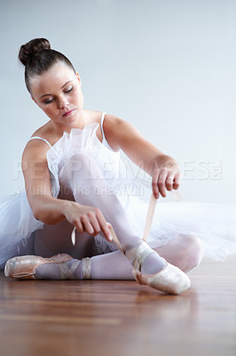 Buy stock photo Portrait of a lady dancer puts on her point ballet shoes - copyspace