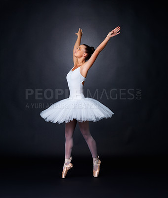 Buy stock photo Full length of a beautiful ballerina dancing gracefully against black background