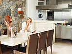 Woman reading book in dining room by kitchen in a modern house