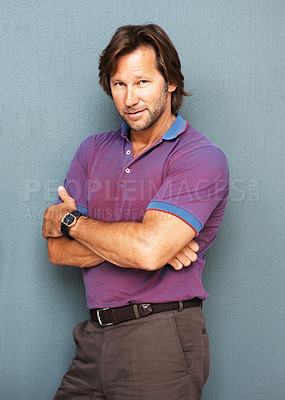 Buy stock photo Portrait of a confident smart mature man with hands folded standing against colored background