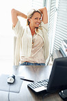 Happy business woman relaxing in front of computer at work desk