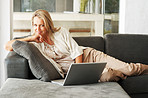 Happy pretty woman lying on sofa while using laptop