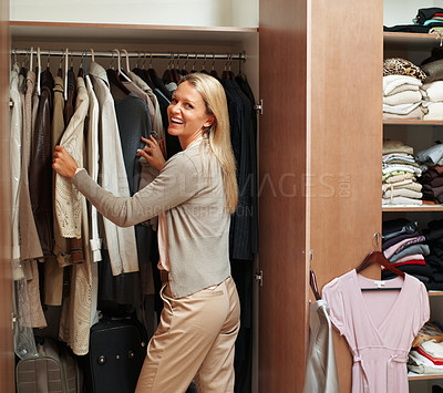 Buy stock photo Portrait of a happy mature female making choices in wardrobe