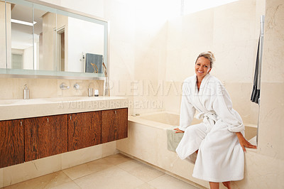 Buy stock photo Portrait of a beautiful smiling mature woman in bathrobe sitting in her modern bathroom