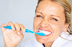 Closeup of a happy attractive woman brushing her teeth