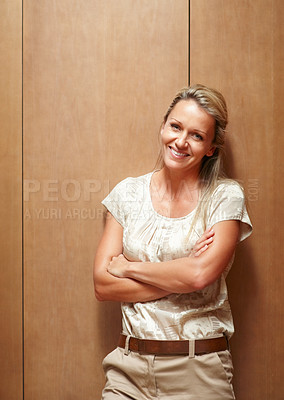 Buy stock photo Portrait of a mature business woman standing with hands crossed against wooden background