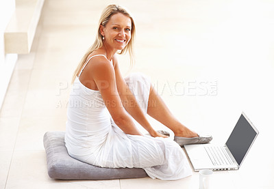 Buy stock photo Portrait of a smiling middle aged woman sitting on floor using laptop