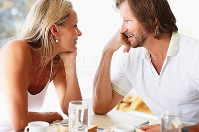 Buy stock photo Portrait of a romantic mature couple looking at each other at dining table
