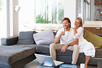 Relaxed mature couple sitting together on couch at home