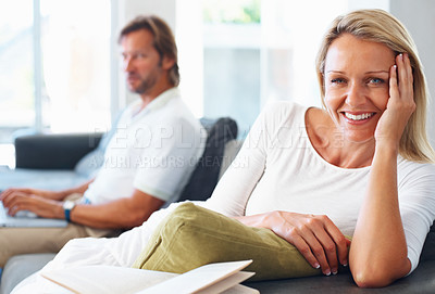 Buy stock photo Portrait of a happy mature lady with man using laptop in the background at home